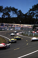 LE MANS, FRANCE: A group of cars follows the pair of Martini Racing Lancia LC2-84s through the esses headed toward Tertre Rouge at Circuit de la Sarthe during the 24 Hours of Le Mans in Le Mans, France, on June 17, 1984.