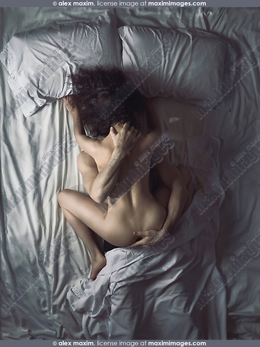 Artistic overhead erotic photo of a couple making love in bed in a dimly lit bedroom with moonlight coming from the window