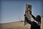 © Remi OCHLIK/IP3 - Bin Jawaad March 27, 2011 - Rebel fighters throw stones and shoot bullet in Qadhafi portraits...Libyan fighters celebrate as they just took back the city of Bin Jawaad without fighting, they found the city empty from the loyalist Khadafi forces