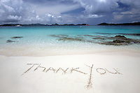 September 2008: Thank You saying written in the white sand near clear blue waters on St. John US Virgin Islands beach scenes.  Stock photos available.