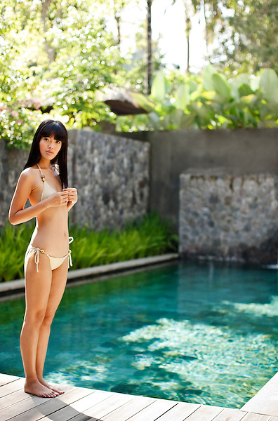 Young Asian woman standing by pool of Bile Deluxe Pool Villa, a private pool villa at Kayumanis Ubud, Bali, Indonesia.