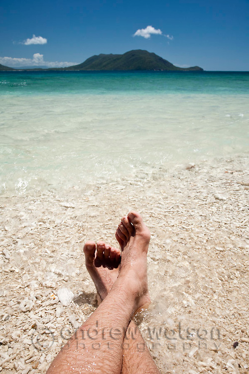 Relaxing on the coral sand of Nudey Beach.  Fitzroy Island National Park, Cairns, Queensland, Austtralia