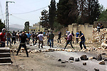 Palestinian protesters throw stones towards Israeli soldiers during clashes following a protest against the expropriation of Palestinian land by Israel on March 31, 2013 in the village of Kfar Qaddum, near the occupied West Bank city of Nablus. Photo by Nedal Eshtayah