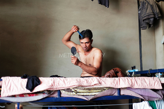 11/10/2014 -- Kirkuk, Iraq -- A Bangladeshi worker brushes his hair after taking a shower in his bedroom during the two hours break he has in the afternoon.