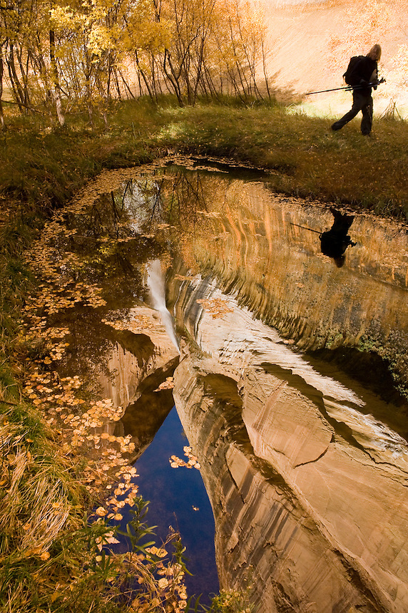 Photography student Joe Decker, of San Jose, Calif., reflects as he passes a small pond while photographing early light on Calf Creek Falls. The falls are a three-mile trail in the Calf Creek Recreation Area near Grand Staircase-Escalante National Monument in southern Utah.