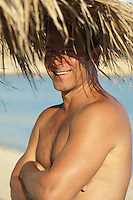 man without a shirt smiling while standing under a palm tree in Mykonos, Greece