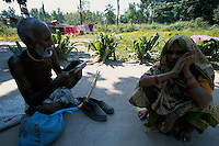 Hindus priest reading prays to a old woman in the suburb of the Maya Devi Temple in Lumbini Nepal, marks the birth place of Siddhartha Gautam Buddha..In 1976, the Nepalese Government and UNESCO designated Lumbini as a world heritage site..-The full text reportage is available on request in Word format