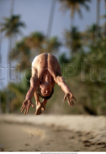 Man doing a BACK FLIP along a beach, 97. Photo: Chris Cole/Action Plus....1997.somersault.model released.leisure activities.pastime.pastimes.fitness.exercise.exercising.lifestyle.work-out.work out.working out.working-out.model released.model release.recreation.male