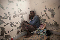 November 20, 2014 - Misrata City, Libya: A Sub-Sahara migrant who is mental illness sits on a mattress in a corridor inside a detention center at the outskirts of Misrata. Libya's revenues from smuggling trade including human trafficking is up to 10% of the national GDP, making this one of the most profitable illegal business across the country. In spite of the international concern of human rights violations, Sub-Saharan migrants risk their lives across Libya, often jailed, sold and kidnapped during their hazardous trip through the Sahara desert to the coastal ports as most of them attempt to reach Europe. (Photo/Narciso Contreras)