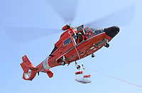 A United States Coast Guard HH-65C Dolphin helicopter lowers a rescue basket to the deck of a Coast Guard Auxiliary vessel. The helicopter and crew, based at U.S. Coast Guard Air Station San Francisco, was on a practice mission with the Coast Guard Auxilary to maintain search and rescue proficiency. Photographed 04/08
