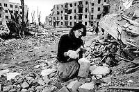En tjsetsjensk kvinne samler murstein fra ruinene av et hus, for a? selge de videre. Krigen har lagt det meste av Grosny i ruiner....