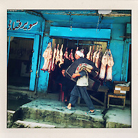 A man carries a rug over his shoulder as he walks past a line of carcasses hanging outside a butchers shop.