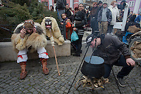 A local man in traditional buso dress talks on his phonee during the Buso Carnival in Mohacs, about 200 km south from the capital city Budapest on March 02, 2014. ATTILA VOLGYI