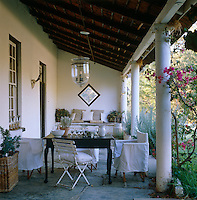 A simple seating area is grouped on the stoep or terrace beneath a thatched roof
