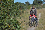 Peter Makura navigates along a path near his home in the village of Berejena, near Masvingo, Zimbabwe, with help from Sonica Sadzauchi, a community rehabilitation worker for the Jairos Jiri Association, which provided Makura with his wheelchair with support from CBM-US.