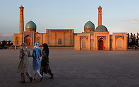 """Women wearing traditional muslim clothes cross the Khast Imam Square, Taskent, Uzbekistan. In the background stands the Khast Imam Mosque, 16th century, seen in the late afternoon summer light on July 4, 2010. Tashkent, 2000 year old capital city of Uzbekistan, a Silk Road city whose name means """"Stone Fortress"""", is now very modern due to a disastrous earthquake in 1966, after which it was greatly rebuilt. However, some of the old buildings still stand in the glittering modern city."""