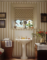 A Victorian style pedestal washbasin stands below a window in a bathroom with striped wallpaper.