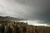 Punakaiki coastline under rain and stormy clouds with pancake rocks in foreground, Paparoa National Park, Buller Region, West Coast, South Island, New Zealand, NZ