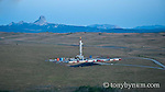 oil drilling rig drilling on blackfeet reservation glacier national park background