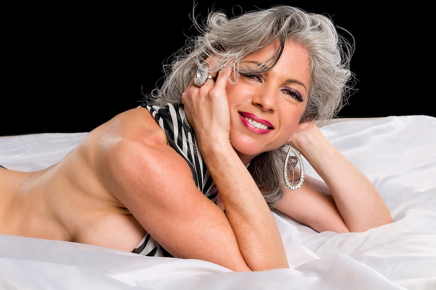Very attractive mature woman smiling in bed.