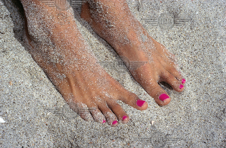 A youthful woman's feet with pink painted toenails in the white sand at the beach.