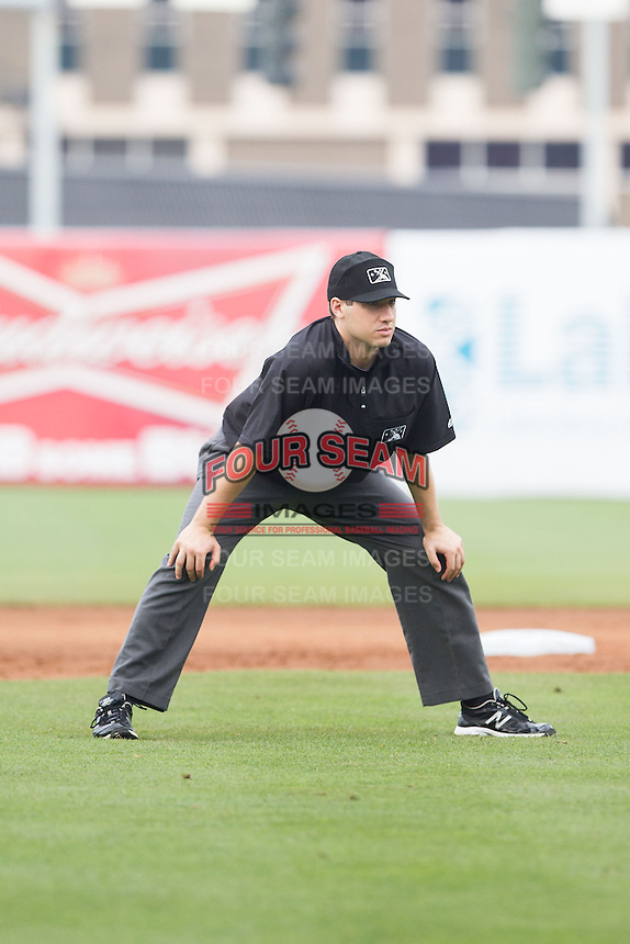 Umpire Jon Felczak handles the calls on the bases during the South Atlantic League game between the Hagerstown Suns and the Greensboro Grasshoppers at NewBridge Bank Park on May 20, 2014 in Greensboro, North Carolina.  The Grasshoppers defeated the Suns 5-4. (Brian Westerholt/Four Seam Images)