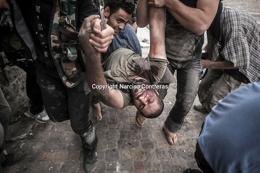 Rebel fighters carry out one Syrian civilian as they take him away from the line of fire. The civilian was shot twice, at his stomach and at his back, by one Syrian army sniper while was walking at the front line in Bustan Al-Bashar, northeast of Aleppo City.