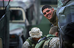 A Marine with the homeward-bound 11th Marine Expeditionary Unit and 1st Battalion 4th Marines smiles as his unit's convoy to Kuwait gathers before departing from Najaf, Iraq after an eight-month-long deployment there on February 1, 2005.
