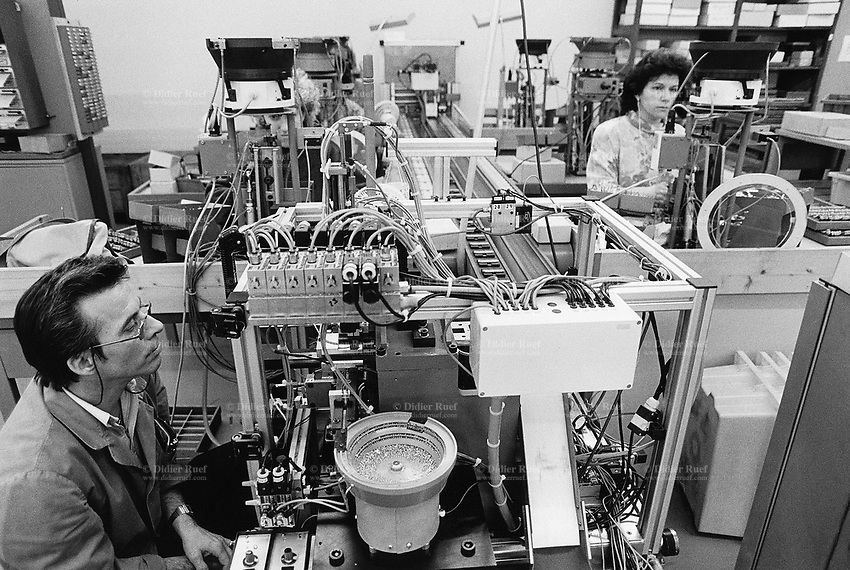 Switzerland. Canton Jura. Delémont. Wenger SA is a factory where is manufactured the famous swiss army knife. A man checks the good functionning of a machine, while two women workers assemble by hand the knifes. © 1992 Didier Ruef