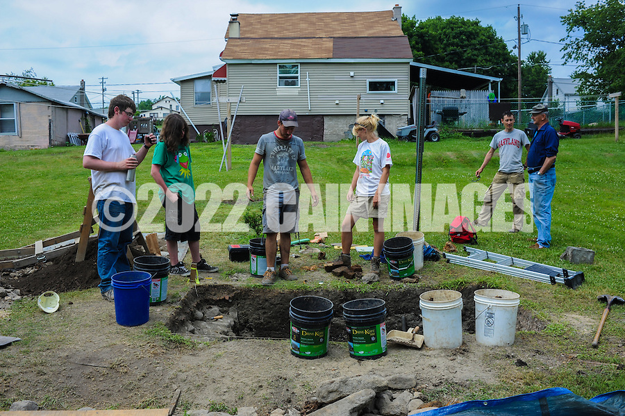 HAZLETON, PA - JUNE 30:  From left, Adam Yeager, Jonathan Nick, Justin Uehlein, Camille Westmont and  Mike Roller work at the site of an archaeologic dig as a neighbor watches June 30, 2014 in Hazleton, Pennsylvania. The team is looking through sites connected with the Lattimer Massacre which occurred in 1897. (Photo by William Thomas Cain/Cain Images)