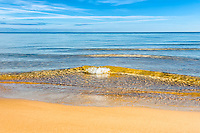 Wave breaking onto a deserted beach in close up, golden water and blue sky make an image of beautiful solitude.