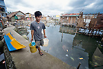 """A man carries water to his home in Tacloban, a city in the Philippines province of Leyte that was hit hard by Typhoon Haiyan in November 2013. The storm was known locally as Yolanda. The man's house lies within a controversial 40 meter """"no build"""" zone. The ACT Alliance has been active here and in affected communities throughout the region helping survivors to rebuild their homes and recover their livelihoods."""