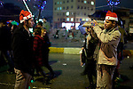 IRAQ, SULAIMANIYAH:  Two teenagers wearing Santa Claus hats take pictures of each other in the streets of Sulaimaniyah to celebrate the new year...Revelers brought in the new year all across Kurdistan with shows of fireworks and enormous street parties...Photo by Metrography