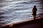 Solitary woman standing on ledge of seawall, looking into  ocean waves.