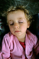 Two year old girl sleeping, France.