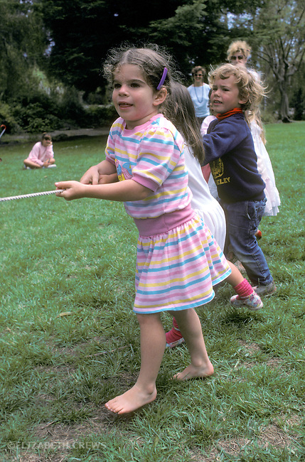 Berkeley CA 4-yr-old girl playing tug-o-war with friends at her birthday party