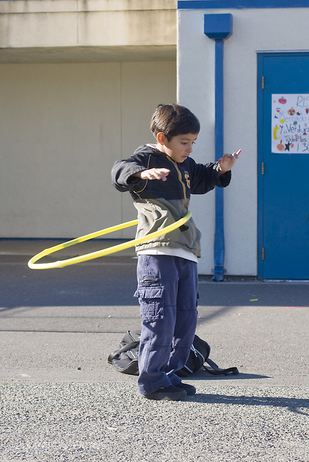 Oakland CA  2nd grade Latino boy playing with hoola hoop at school recess