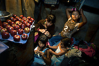 Luisa Fernanda (stage name Yasuri, centre top) braids the hair of her sister as the circus owner's children look on next to a plate of apples at the Jhon Danyer Circus. Luisa and Karin have been adopted by the circus owner after they were left virtually abandoned. Luisa performs as a contortionist, does aerial displays and also sells snacks to the audience before and during the performance. Around a dozen small circuses wander the poorer neighbourhoods around the city of Medellin putting on performances in what can be a hand to mouth existence. Despite falling audience numbers, new health and safety regulations and other bureaucracy these small family businesses, many of whom have existed for generations, still scrape a living in a world where the people are more accustomed to being entertained by soap operas than by live entertainment.