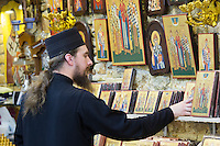 Greek Orthodox priest with religious art icons in souvenirs and gifts shop in Kerkyra, Corfu Town, Greece