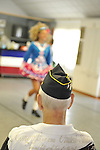 Focus on back of American Legionaire, as he watches Irish step dancer, a young girl seen in soft focus in colorful costume, from the Hagen School of Irish Dance, at barbecue hosted by Merrick Post #1282 of American Legion for veterans from New York State Nursing Home at Stony Brook NY, on August 13, 2011, in Merrick, New York, United States. Photo © 2011 Ann Parry, All rights reserved. Ann-Parry.com