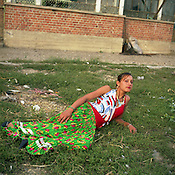 "A Roma girl lays on the grass, pretending to pose like a ""western"" model, in the Roma community of Sintesti.."