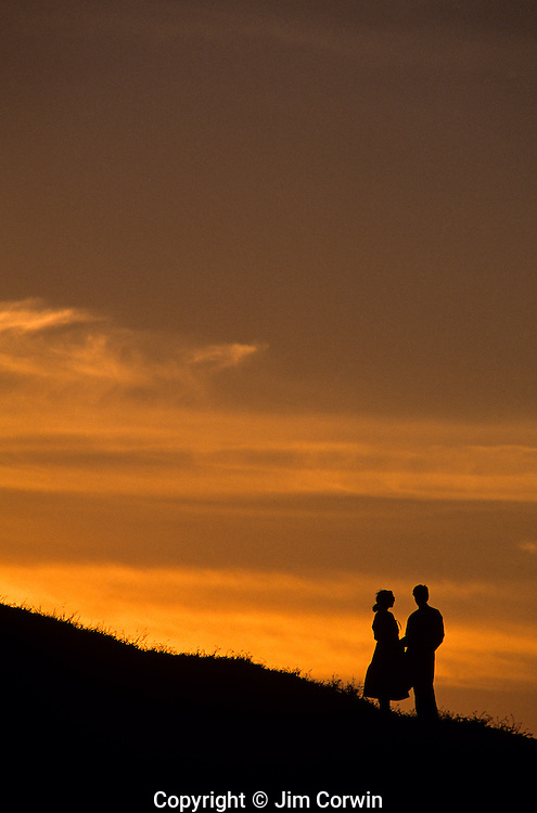 Silhouetted woman  and man at sunset standing on bluff