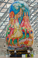 Moscow, Russia, 15/06/2011..A woman photographs an exhibition of of giant Russian matryoshki, or nesting dolls, in the newly-opened Afimall shopping centre. The dolls, designed by Boris Krasnov, are from 6 to 13 metres high, and each is decorated in a different style of traditional Russian folk art. This doll is decorated in the Mstero style.