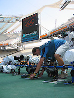 A photographer places a remote camera on the field prior the start of events  at Olympic stadium in Athens, Greece Sunday August 29, 2004. (2004).