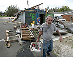 After Hurricane Gustav  made landfall, Frog Carlos, carries litter away from what used to be his bar in Houma, Louisiana September 2, 2008    (Mark Wallheiser/TallahasseeStock.com)