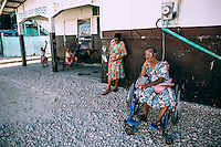 A woman sits in her wheelchair while children play nearby.