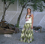 Roxana, a young married Roma woman, wears a risque t-shirt instead of the more traditional style of clothes favoured by Roma women, in the Roma community of Sintesti. She stands in the garden of her husbands fmaily home, beside scrap metal, part of her husbands's scrap metal business..