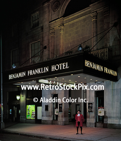 Man in a Ben Franklin costume standing outside hotel