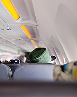 Rastafarian hat wearer sitting a few rows ahead of the camera on a plane.
