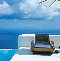 A wooden sun lounger has been placed next to the infinity pool with an idyllic view over the Mediterranean